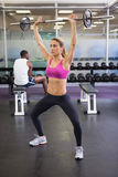Full length of fit woman lifting barbell in gym Stock Photo