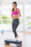 Full length of a fit woman performing step aerobics exercise Stock Image