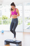 Full length of a fit woman performing step aerobics exercise Stock Images
