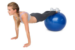 Full length of a fit woman stretching on fitness ball Stock Photo