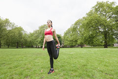 Full length of fit young woman performing stretching exercise in park Royalty Free Stock Images