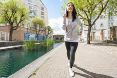 Full length of fit young woman running by canal Royalty Free Stock Photos