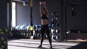 Full length of fitness girl in sportswear doing crossfit workout with 10 kilo kettle bell. Lifting high under the head stock video footage