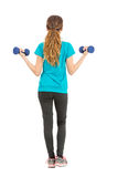 Full length fitness woman rearview lifting dumbbells Royalty Free Stock Photography