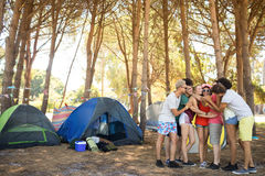 Full length of friends embracing. While standing on field at campsite Royalty Free Stock Photo