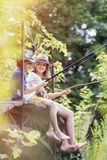 Full length of friends fishing while sitting on pier royalty free stock photography