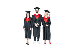 Full length front view of happy students in graduation caps standing together Royalty Free Stock Image