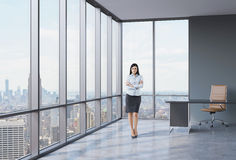 Full length of the girl with crossed hands is standing in the corner panoramic office. Stock Photos