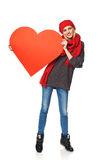 Full length girl holding up a red cardboard heart Stock Photo