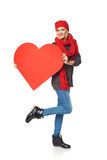 Full length girl holding up a red cardboard heart Royalty Free Stock Photos