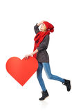 Full length girl holding up a red cardboard heart Royalty Free Stock Photo