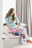 Full-length of girl trying to close suitcase at home Royalty Free Stock Images