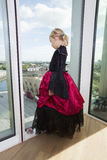 Full length of girl in vampire costume looking out through window at home Stock Image