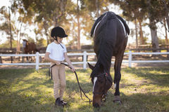 Full length of girl wearing helmet standing by horse. On field in paddock stock photo