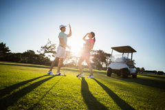 Full length of golf player couple giving high five. While standing on field Royalty Free Stock Image
