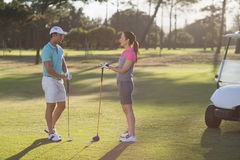 Full length of golf player couple. Standing on field Stock Image