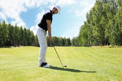 Full length of golf player playing golf on sunny day. Professional male golfer taking shot on golf course.  stock photos