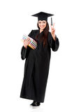 Full length graduation girl. Beautiful graduate girl student in mantle with books showing victory sign, isolated on white background Stock Photography