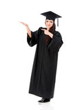 Full length graduation girl. Beautiful graduate girl student in mantle showing something, isolated on white background Royalty Free Stock Image