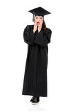 Full length graduation girl. Full length emotional portrait of a young amazed or surprised graduation girl in mantle isolated on white background Royalty Free Stock Image