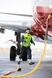 Crew Member Walking By Airplane Being Charged On Runway. Full length of ground crew member walking while airplane being charged on runway royalty free stock photo