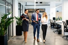 Full length of group of happy young business people walking the corridor in office together. Full length of group of happy business people walking the corridor royalty free stock images