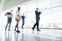 Full length of group of happy young business people walking the corridor in office together. Walk team. stock images