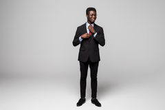 Full length of handsome young African man in smart casual jacket make his tie while standing against grey background Royalty Free Stock Photos