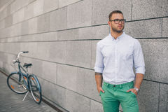 Full length of handsome young businessman with his bicycle. Cycling by the street. Full length of handsome young businessman with his bicycle Stock Photo