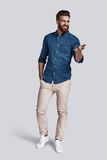 This is it!. Full length of handsome young man gesturing and keeping hand in pocket while standing against grey background Royalty Free Stock Photo