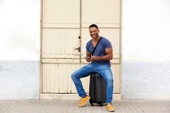 Full length happy african man sitting on a suitcase with mobile phone and smiling. Full length portrait of happy young african man sitting on a suitcase with Stock Photo