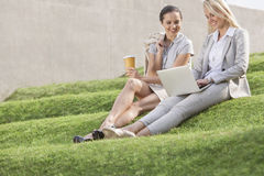 Full length of happy businesswomen looking at laptop while sitting on grass steps against wall Royalty Free Stock Photo