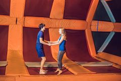 Full length of a happy couple jumping on trampoline royalty free stock image