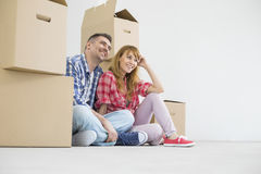 Full-length of happy couple sitting in new house royalty free stock image