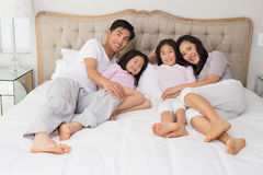 Full length of a happy family of four lying in bed. Full length portrait of a happy family of four lying in bed at home royalty free stock photo