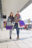 Full length of happy female friends with shopping bags walking on sidewalk Stock Photo