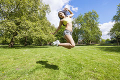 Full length of happy fit woman jumping in park Royalty Free Stock Photography