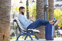 Full length happy man with cellphone and suitcase sitting on bench Stock Images
