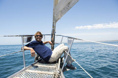 Full-length of happy man sitting on bow of yacht Stock Photos