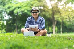 A happy smiling mid aged man sitting in park hold royalty free stock photos