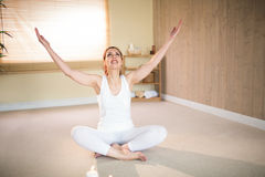 Full length of happy woman meditating with arms raised Royalty Free Stock Photo