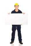 Full length happy worker presenting empty banner.  Royalty Free Stock Photo