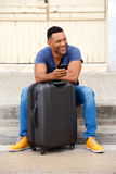 Full length happy young african man sitting with suitcase and mobile phone. Full length portrait of happy young african man sitting by the road with suitcase and Stock Image
