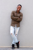 Full length happy young black guy smiling against gray wall Royalty Free Stock Photos