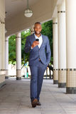 Full length happy young business man walking with mobile phone. Full length portrait of happy young african business man walking with mobile phone Royalty Free Stock Photography