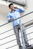 Full length of happy young businessman using mobile phone at balcony Stock Photos