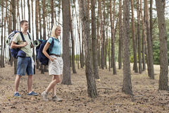Full length of happy young couple hiking in forest Stock Images