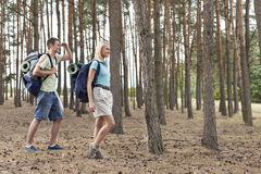 Full length of happy young couple trekking in forest Royalty Free Stock Photos