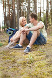 Full length of happy young hiking relaxing in forest Stock Image