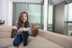 Full length of happy young woman playing video game on sofa at home Royalty Free Stock Image